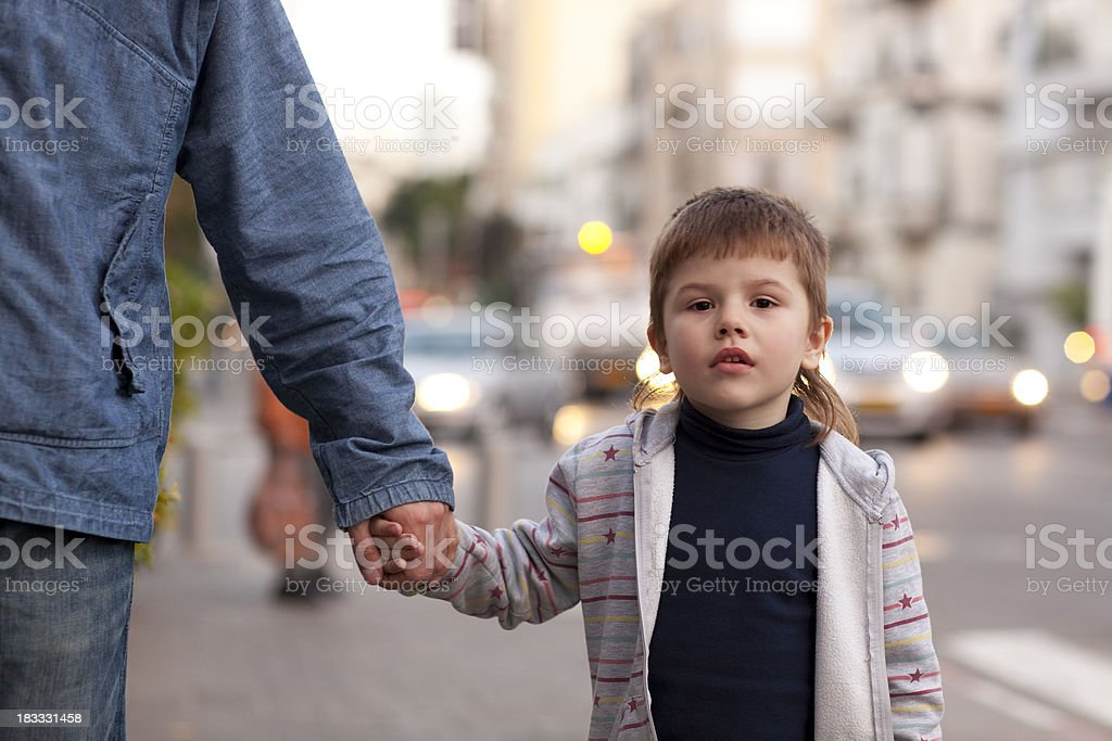 Boy holding Father's hand at street. royalty-free stock photo
