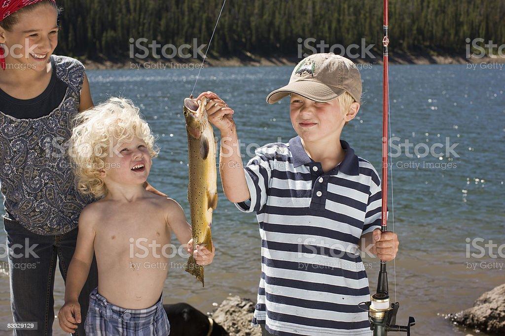 Ragazzo tenendo il pesce ha catturato foto stock royalty-free