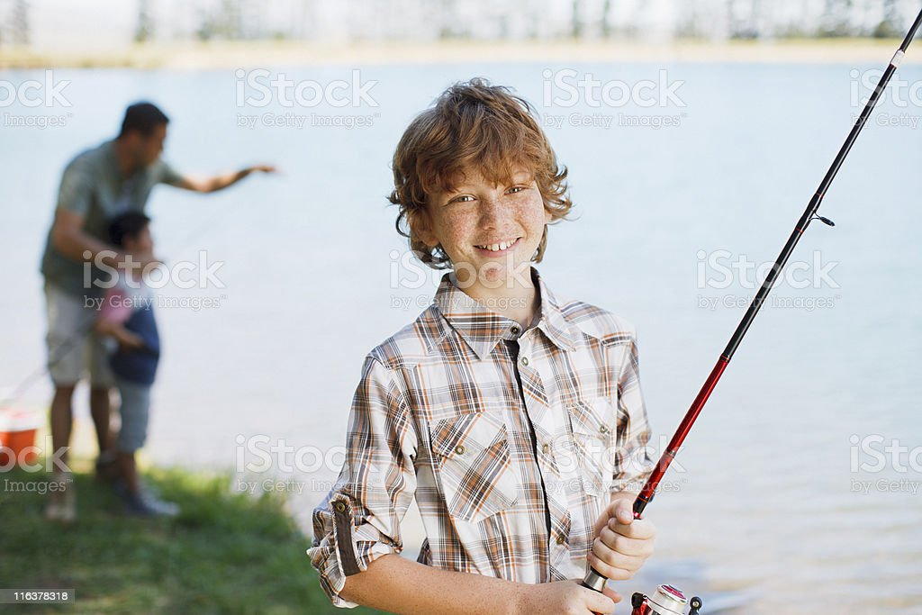 Boy holding fishing rod near lake stock photo