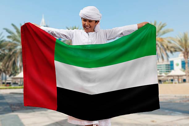 мальчик держит флаг - uae flag стоковые фото и изображения