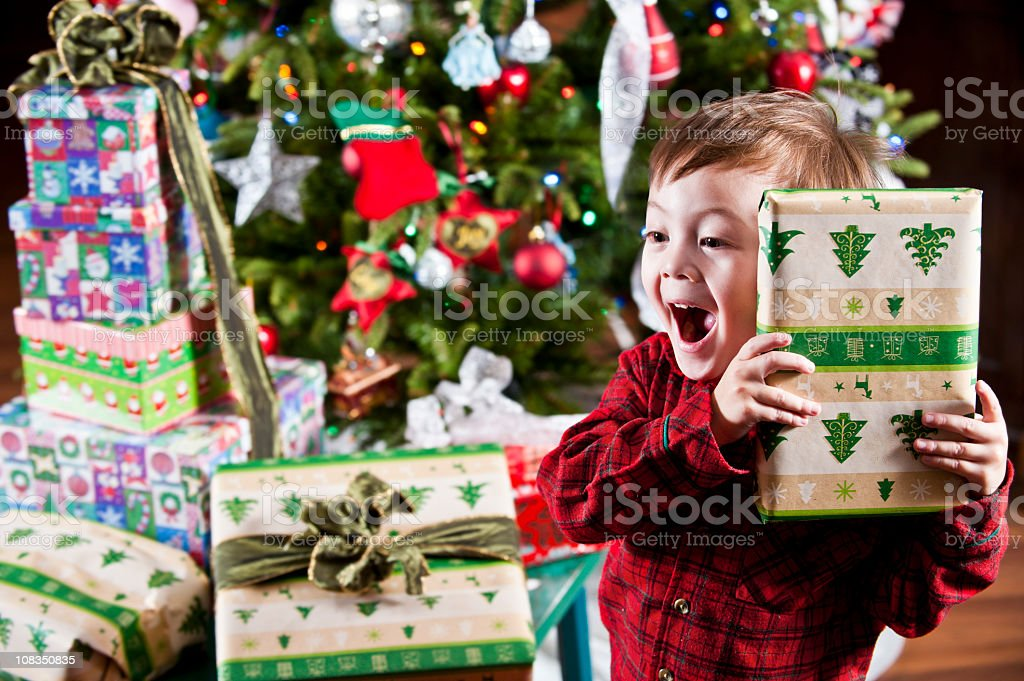 Boy holding gift to ear in front of Christmas tree and gifts stock photo