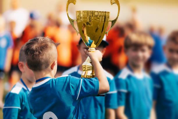 boy holding golden trophy en het vieren van sport succes met team - internationale voetbal stockfoto's en -beelden