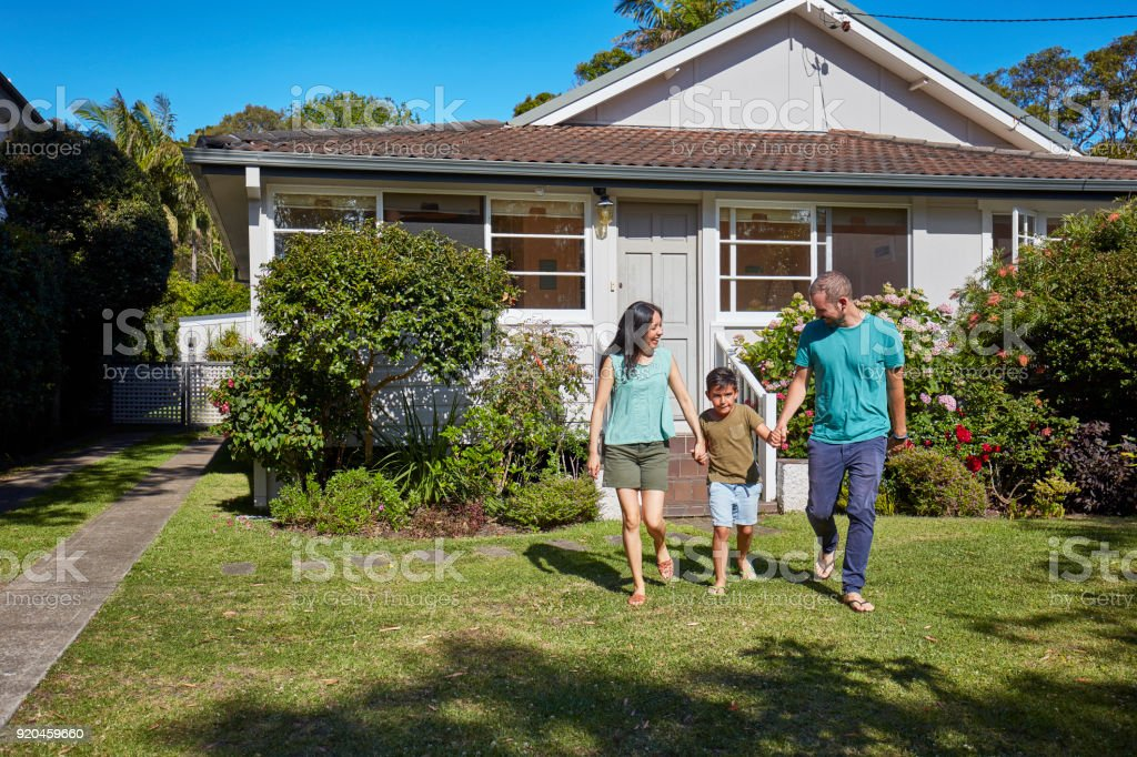 Boy holding hands of parents while walking in lawn stock photo