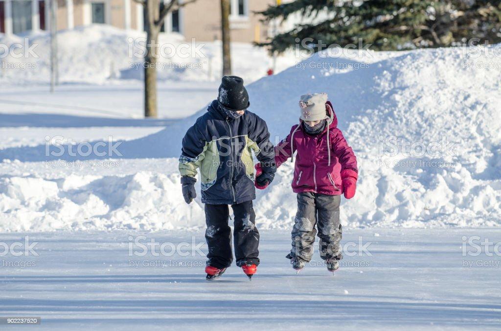 Jungen an Hand ihrer Schwester zu helfen, ihre Eislaufen – Foto