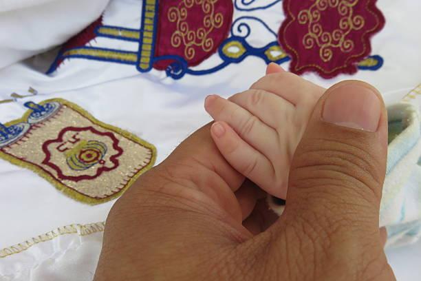 garçon tenant la main de son père en circoncision - circoncision photos et images de collection