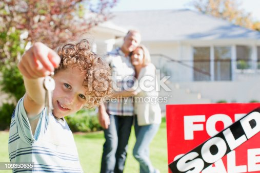 istock Boy holding new house keys next to sold sign 109350635