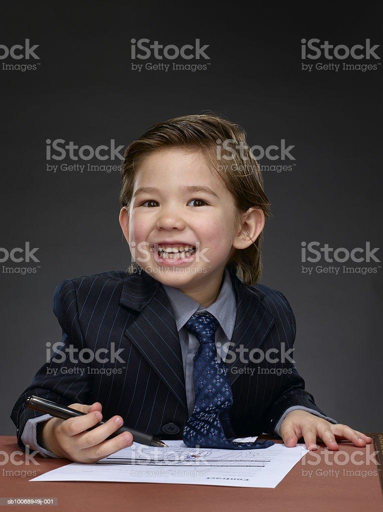 Boy (2-3) holding pen, smiling foto de stock libre de derechos