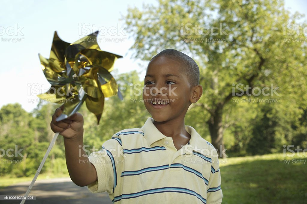 Boy (4-5) holding pinwheel, smiling royalty free stockfoto