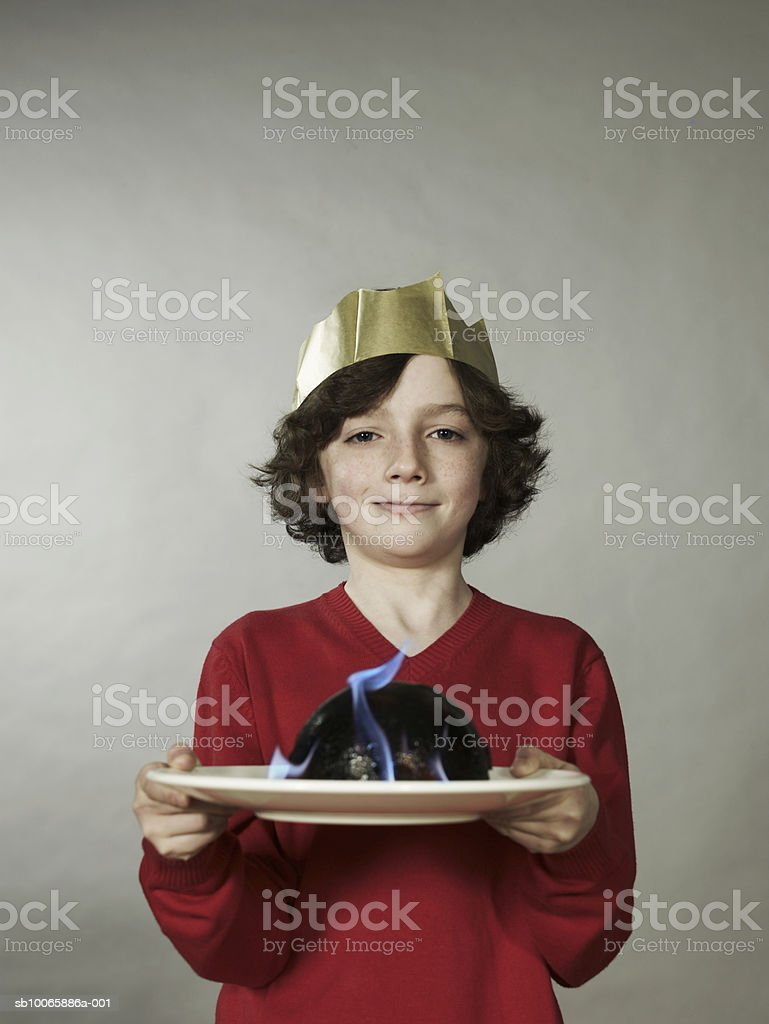 Boy (8-9) holding plate, smiling, portrait foto royalty-free