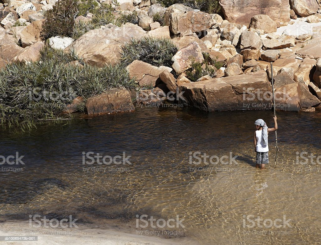 Boy (6-7) holding pole standing in stream, elevated view royalty-free stock photo