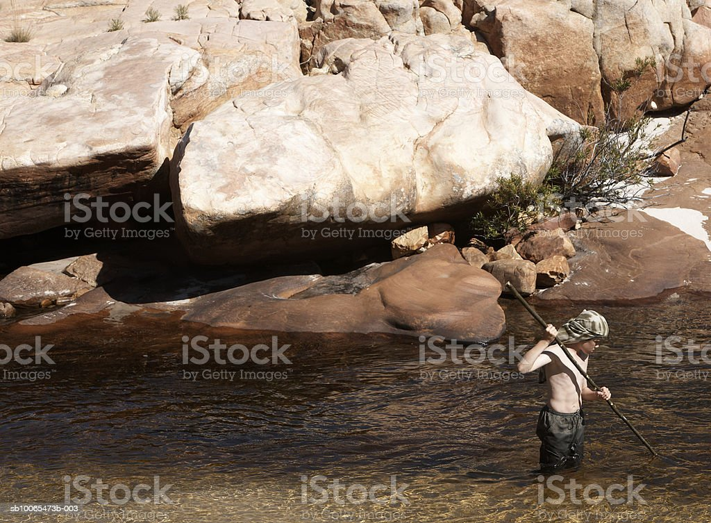 Boy (12-13) holding pole standing in stream, elevated view royalty-free stock photo
