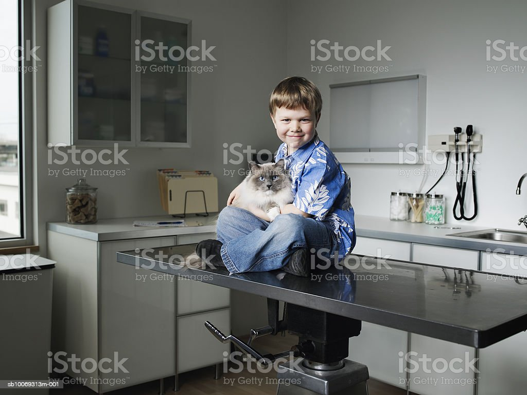Boy (4-5) holding Ragdoll cat in veterinarian exam room royalty-free 스톡 사진