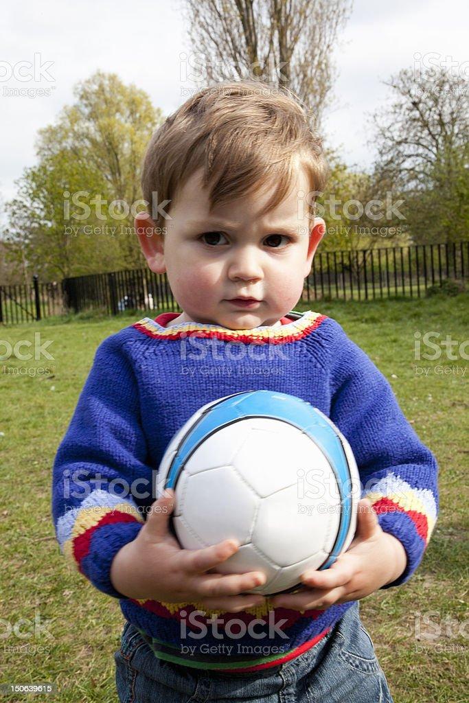 Boy holding soccer ball in backyard stock photo