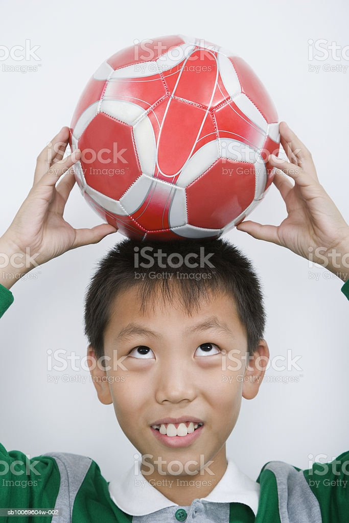 Boy (10-11) holding soccer ball on head foto de stock libre de derechos