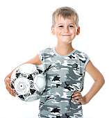 ... Niño que toma de la pelota de fútbol  Irreconocible poco jugador de fútbol  con césped verde 9dda49375a794