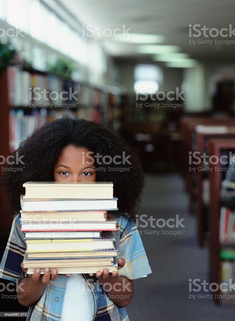Boy holding stack of books royalty-free stock photo