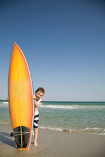 Boy holding surfboard on its end in the sand stock photo