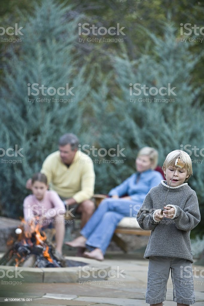 Boy (6-7) holding tongs, family at campfire in background royalty-free stock photo