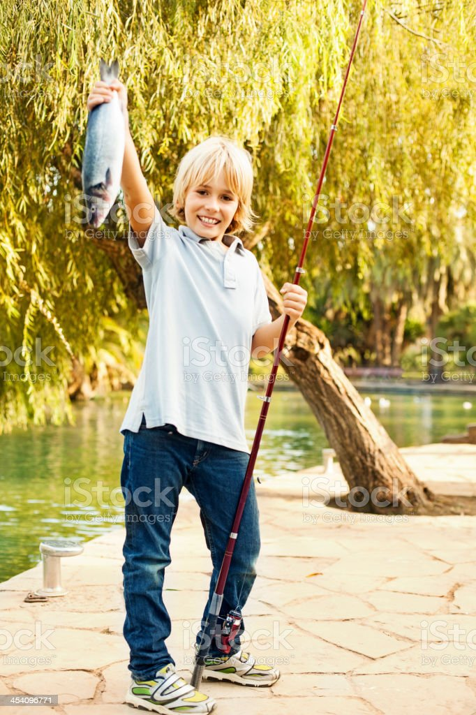 Boy holding up fish royalty-free stock photo