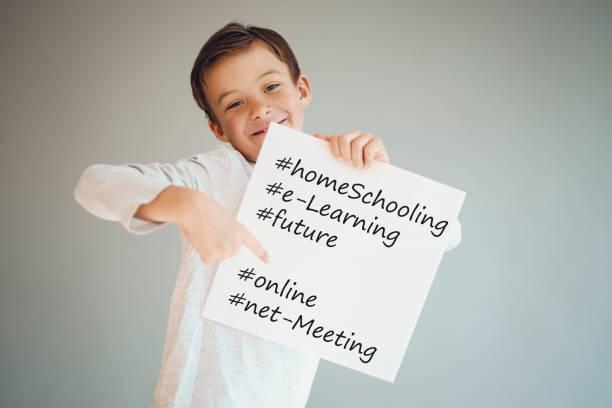 Junge hält weißes Zeichen mit den Worten Homeschooling und mehr – Foto