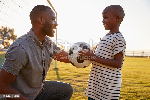 829627936istockphoto A boy holds a football while playing with his dad 829627930