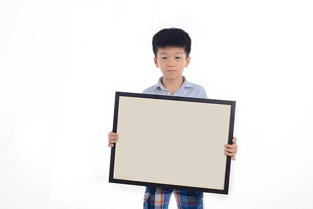 boy holds a wooden blank frame stock photo