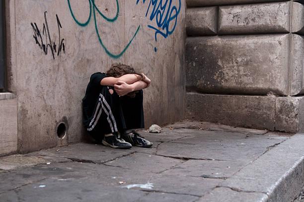 menino huddled e em monoterapia na rua - criança perdida imagens e fotografias de stock