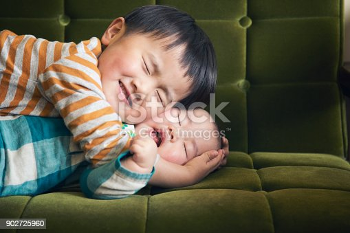 istock Boy hugging baby on sofa 902725960