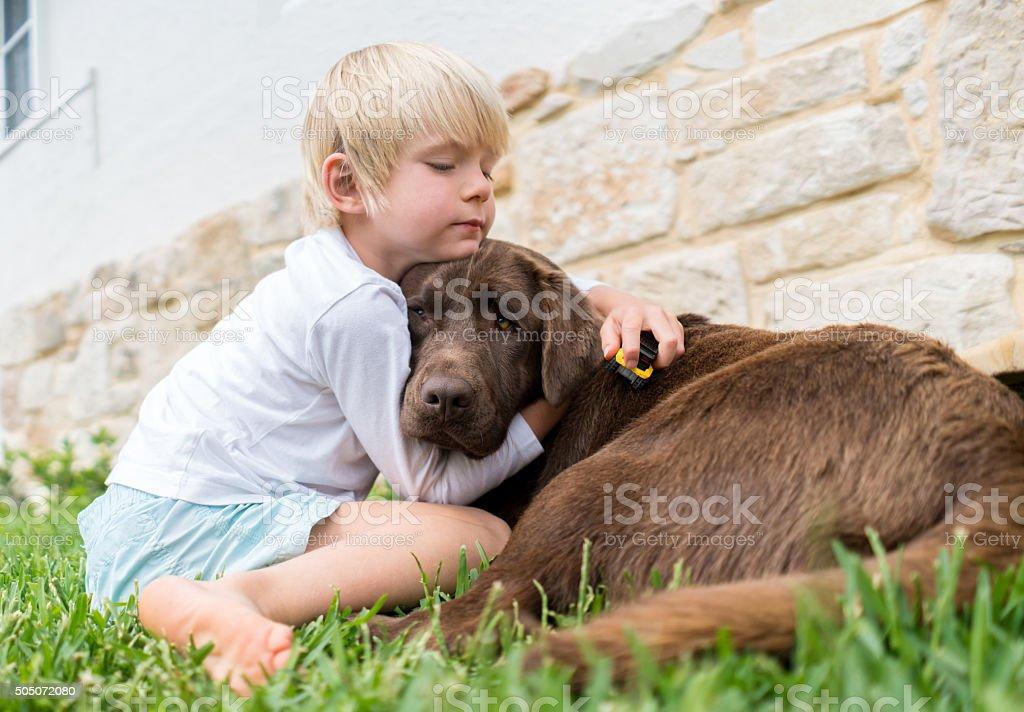 Boy hugging his dog stock photo