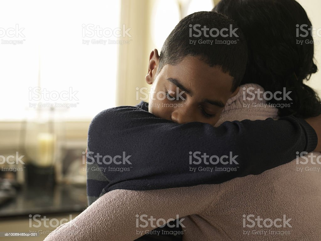 Boy (12-13) hugging mother at home 免版稅 stock photo