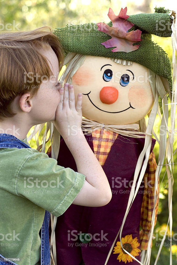 Boy Imagines Friendship with Autumn Scarecrow, Redhead & Freckles Child stock photo