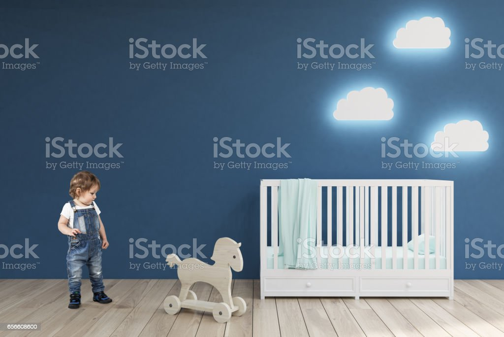 Boy in a baby's room, blue walls stock photo