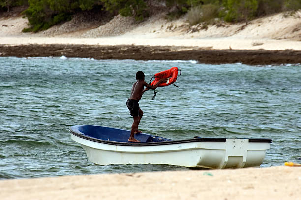 Boy in a Boat Boy playing in a boat on the beach aegis stock pictures, royalty-free photos & images
