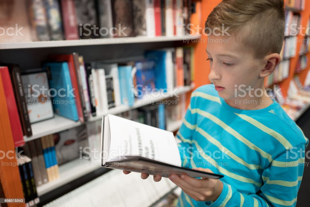 boy in a bookstore stock photo