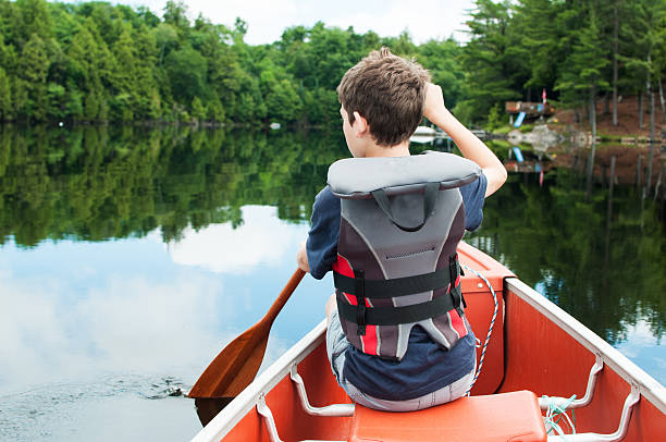 boy in a canoe young boy paddling in a calm lake in the front of a canoe canoeing stock pictures, royalty-free photos & images