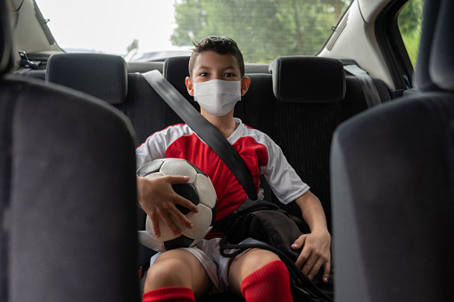 Boy in a car on his way to soccer practice wearing a facemask to avoid the coronavirus pandemic