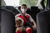 Portrait of a boy in a car on his way to soccer practice wearing a facemask to avoid the coronavirus pandemic – lifestyle concepts