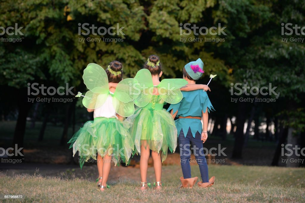 Boy in a costume and two girls in a green fairy costume with wings stock photo