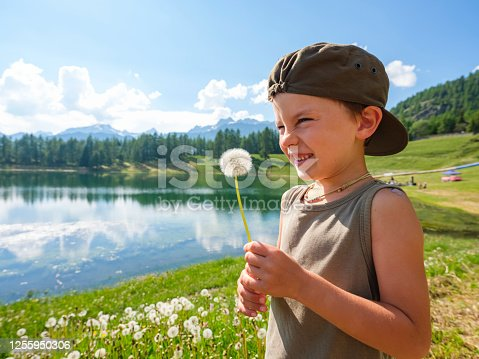 A boy in a hat, near the Lod-Teppa lake in the village of Corgnolaz, in the mountain valley of Aosta, blows a dandelion flower. A dandelion flower is blowing near the mountain lake.