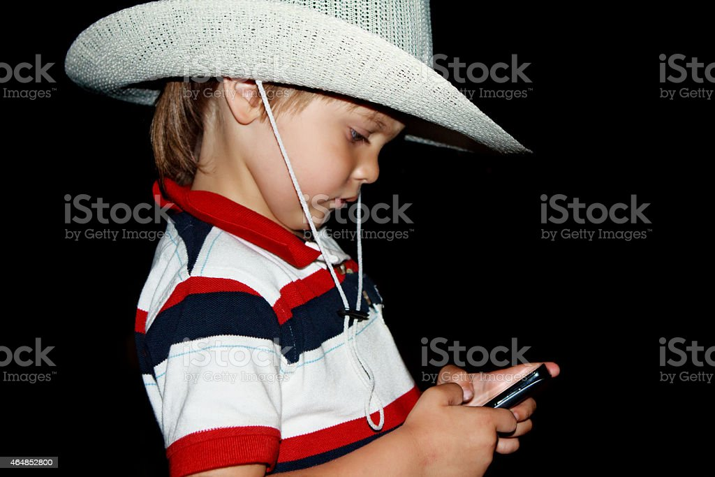 Boy in a hat with a phone stock photo
