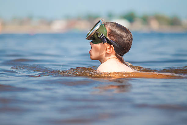 boy in a mask for diving takes a deep breath stock photo