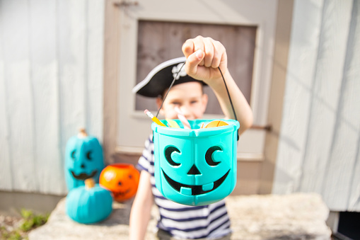 boy in a pirate costume holds a bucket with inedible gifts