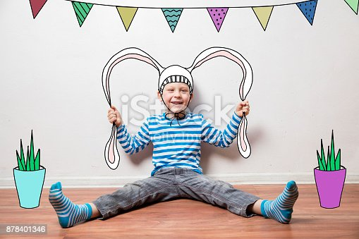 istock Boy in a rabbit costume, pulls his ears 878401346