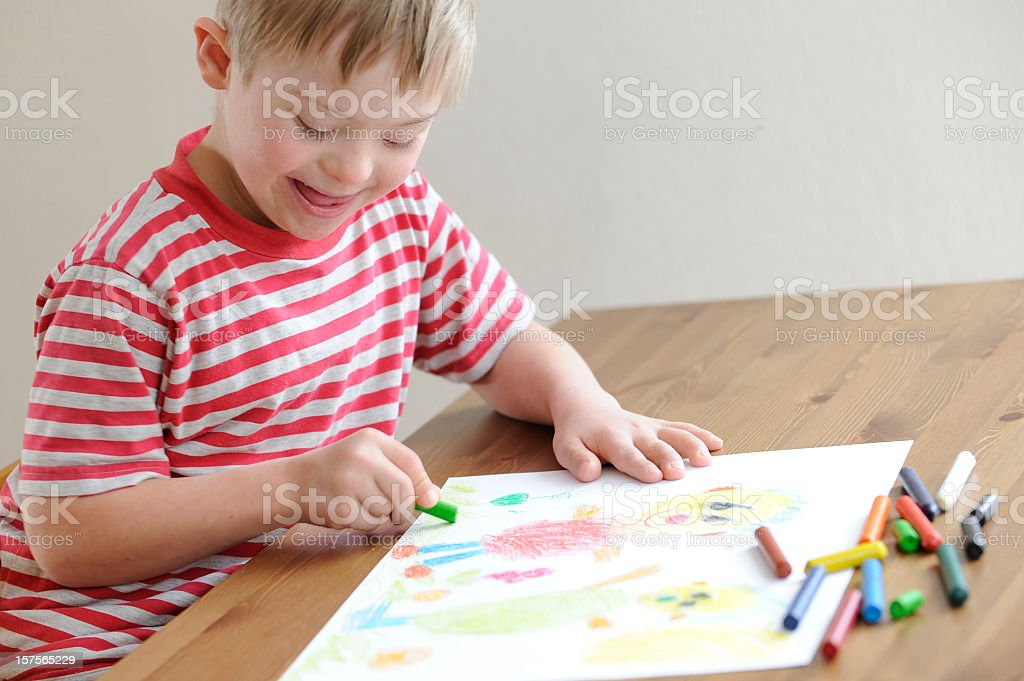 A Boy In Red Stripes T Shirt Coloring With Crayons Royalty Free Stock