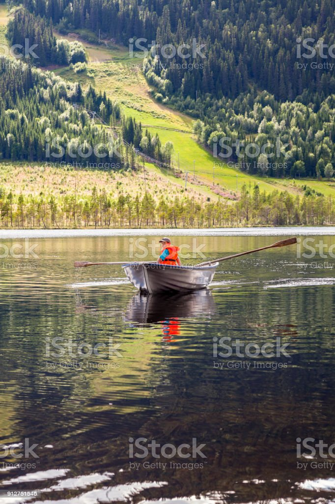Boy in a rowing boat on a mountain lake with green hills and forest. royalty-free stock photo