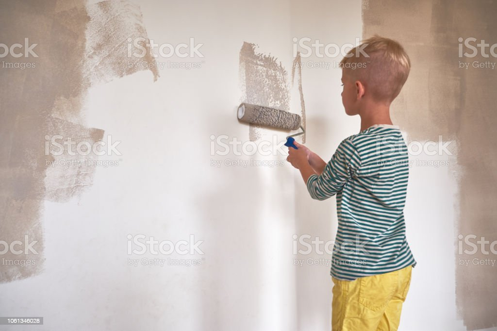 A boy in a striped t-shirt makes home repairs and paints the walls...