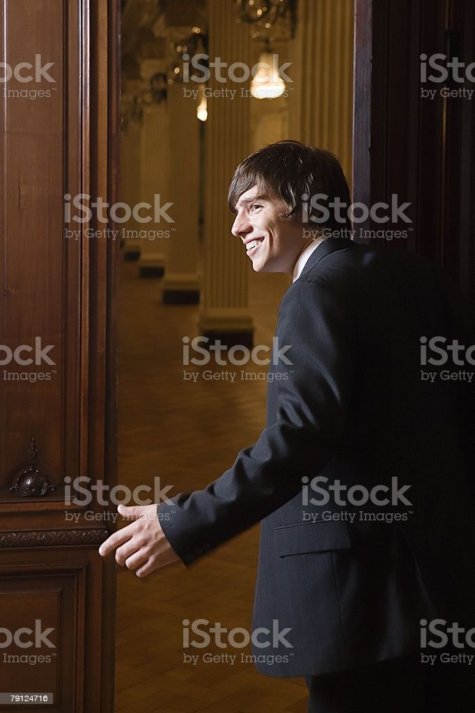 Boy in a suit opening door royalty-free 스톡 사진
