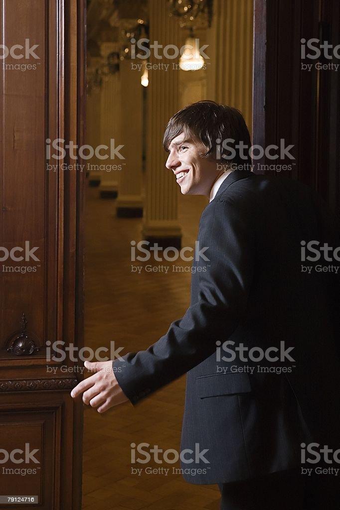 Boy in a suit opening door 免版稅 stock photo