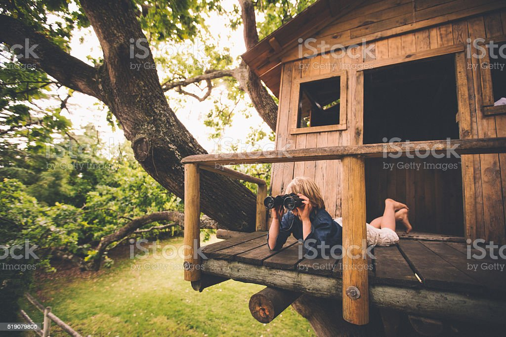 Boy in a treehouse looking in the distance with binoculars stock photo