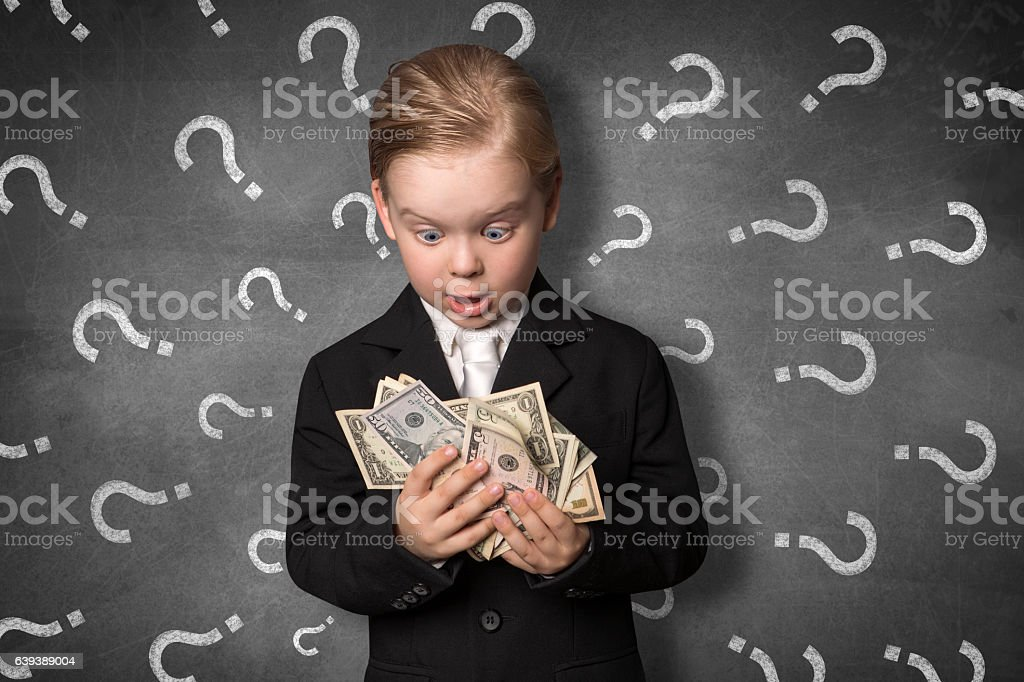 Boy in amazement holding money stock photo